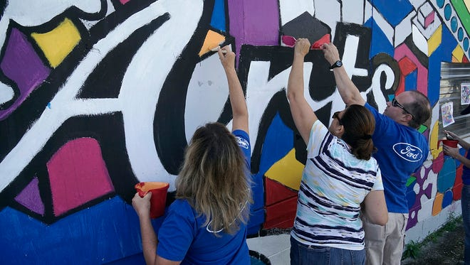Ford volunteers Suzanne Hogan, Samar Sakakini and Matthew Morrison paint the mural on the Village Arts Factory.