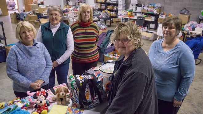 Carol Sharp, in foreground, and her crew of volunteers: Peggy Knivila, Linda Cielieska, Susan Parker, and Brenda Borrusch. All are residents of Westland, except Cielieska, who resides in Dearborn. The cavernous warehouse space is donated to the group.