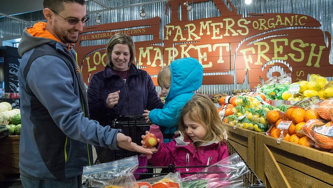 Ben and Kim Smith, with daughters Evelynn and Cecilia, shop for produce at the new Busch's Market. They are from Westland.