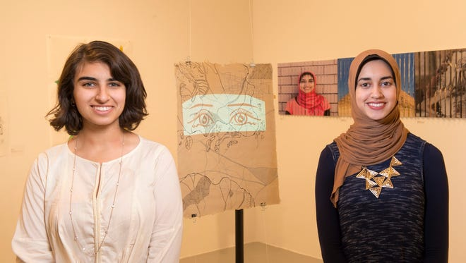 "Muslim Feminists for the Arts Co-President Zahra Bukhara (left) MGSA '18 and Muslim Feminists for the Arts Co-Founder Usra Attalla MGSA '19 at an exhibit of their work, titled ""Beyond East and West"" and ""Where the Lines Shift,"" respectively."