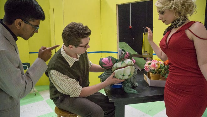 Mr. Mushnik (Abhinand Keshamouni) and Audrey (Hayley Martin) get a close look at the strange plant Seymour Kielborn (Dalton Barthold) found in the wholesale flower district after a total eclipse. The strange plant draws customers to the once failing flower shop.