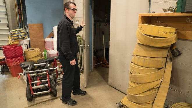 Firefighter Mike Becker closes doors to storage.