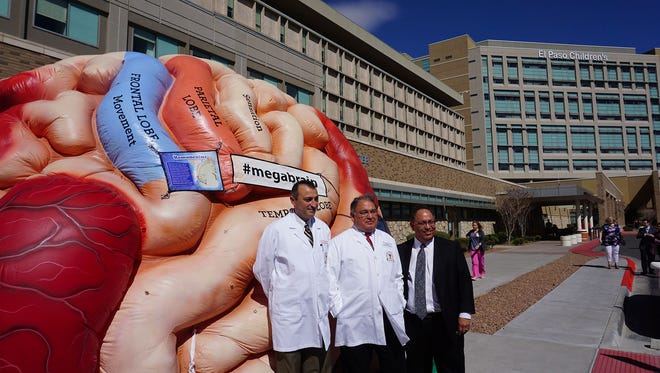 University Medical Center of El Paso Stroke Program Medical Director Alberto Maud, M.D., and Neurocritical Care Medical Director Salvador Cruz Flores, M.D., both faculty of Texas Tech University Health Sciences Center El Paso, stand with UMC President and CEO Jacob Cintron in front of an inflatable brain during an event celebrating UMC's designation as a Comprehensive Stroke Center by The Joint Commission. UMC is the first and only CSC in the El Paso region.
