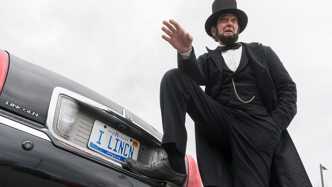 Ron Carley, as Lincoln, rides in a Lincoln.