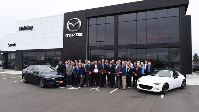 Holiday Mazda staff and leadership were joined by representatives from Mazda North American Operations Midwest Region and ambassadors from Envision Greater Fond du Lac for a ribbon cutting ceremony on Friday, April 27, to celebrate the grand re-opening event. Holding the scissors is Holiday Automotive President Thor Gilbertson, flanked by VP Michael Shannon Jr., left, and General Sales Manager Jeff Gravelle, right.