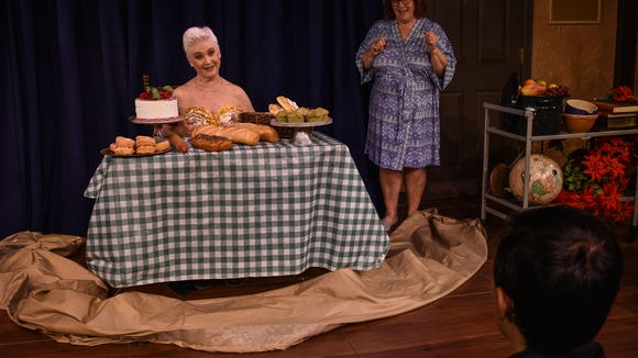 Celia (Wendy Romero) and some strategically placed baked goods are photographed for the calendar as Jessie (Alice Ingle) watches.