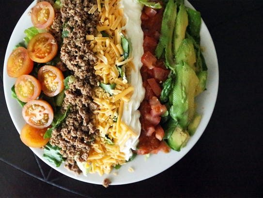 A plate of ground beef cooked in oil with avocados,