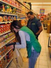 Marilyn Sanchez, left, an employee of Market Fresh in the City of Poughkeepsie, checks the accuracy of store prices with a hand-held price scanner while Jesus Horton, right, the store manager, supervises.