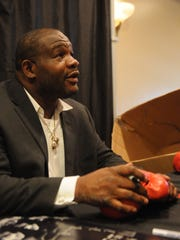 Former heavyweight world champion boxer Riddick Bowe talks with a fan while autographing leather boxing gloves at a special event held at the Arbor Ridge Catering Hall in Hopewell Junction.