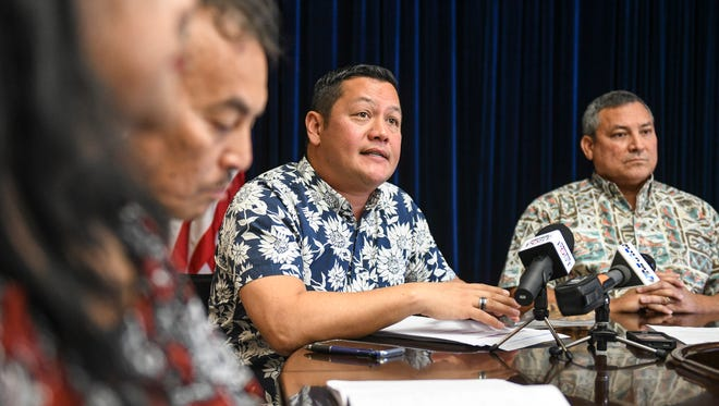 In this March 6 file photo, Jay Rojas, Guam Economic Development authority administrator, announces the government of Guam was put on a credit watch. Gov. Eddie Calvo is shown to the right.