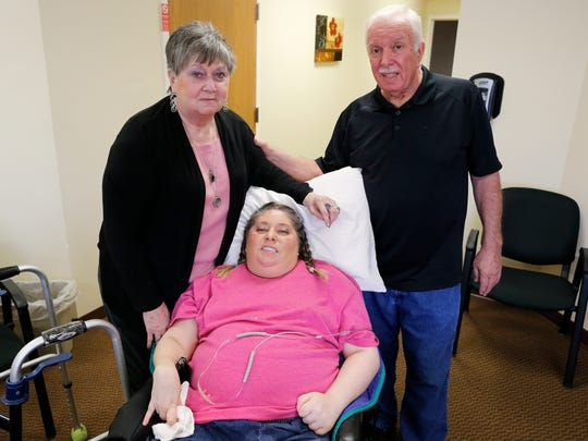Margie Robbins, left, and her husband, Larry, pose with their daughter Melanie Robbins at a nursing home in Florence on Tuesday, April 4, 2017. Robbins was recently awarded $8.2 million in a medical malpractice lawsuit against doctors after a misdiagnosed blood vessel burst in her brain, paralyzing her and giving her brain damage.