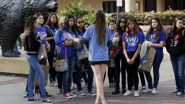In this Feb. 26, 2015, file photo, UCLA campus tour guide Samantha St. Germain, center, a bioengineering student, leads prospective college-bound high school seniors on a campus tour in Los Angeles. The question at many universities is, how many committed students will actually enroll in the fall?