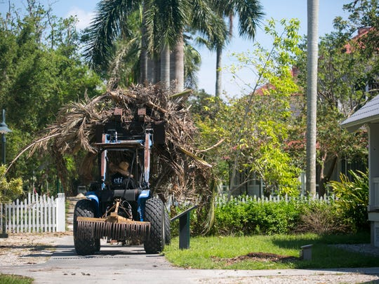 A landscaper removes debris from the Edison side of the Edison & Ford Winter Estates on Wednesday morning in Fort Myers.
