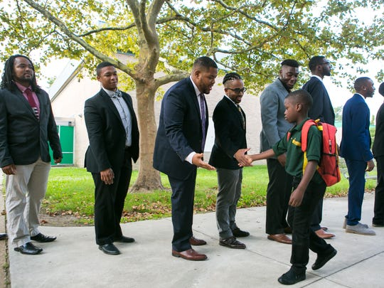 Several dozen black males from around the area dress in suits for Suit Up. Show Up., an event that asked them to step up to model what success looks like by welcoming young students at EastSide Charter School on their first day of school.