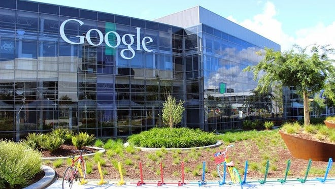 "Glass-walled, multistory Googleplex with ""Google"" written on side of building and a couple bikes in multicolor bike racks in foreground"