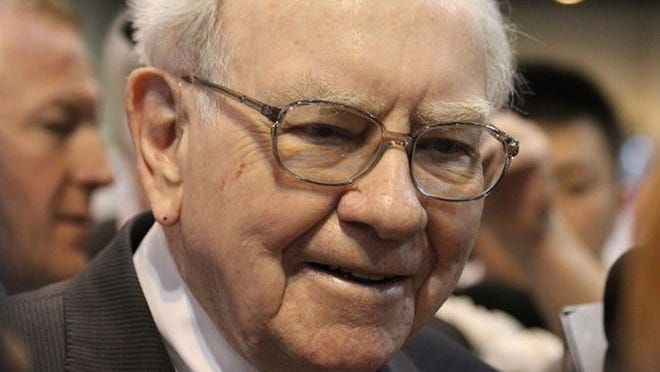 Buffett looks to camera surrounded by fans at a gathering.