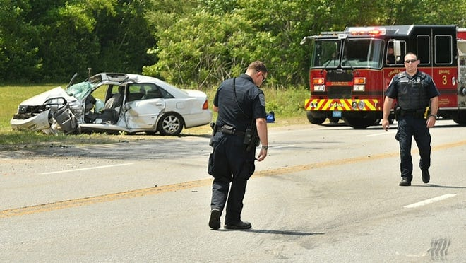 Police examine marks in the road as they investigate a three-vehicle crash on Route 20 in Charlton on Monday.
