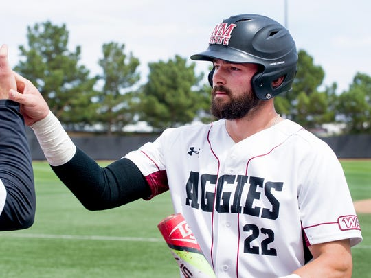 NMSU infielder Caleb Henderson receives a high five after scoring the Aggies first run against the Sacramento State Hornets  Saturday afternoon at Presley Askew Field.