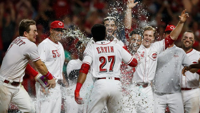 Cincinnati Reds' Phillip Ervin (27) is sprayed with water as he crosses home plate with a walk-off home run off San Francisco Giants relief pitcher Ray Black during the 11th inning of a baseball game Friday, Aug. 17, 2018, in Cincinnati. The Reds won 2-1.