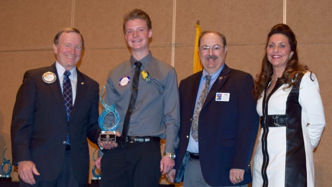 Landon Taylor, second from left, poses with officials from the Rotary Club of Albuquerque after receiving an award recognizing his service to his school and community. Others, left to right, are Rotary Club President Reg Rider, club district governor Tom Walker, and Melanie Burns, vice president of event business partner Achievement Gallery.
