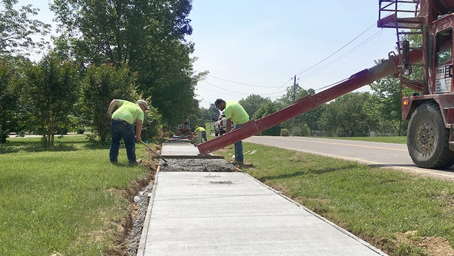 Crews work to complete a Safe Routes To School sidewalk project along Cumberland Drive in Fairview.