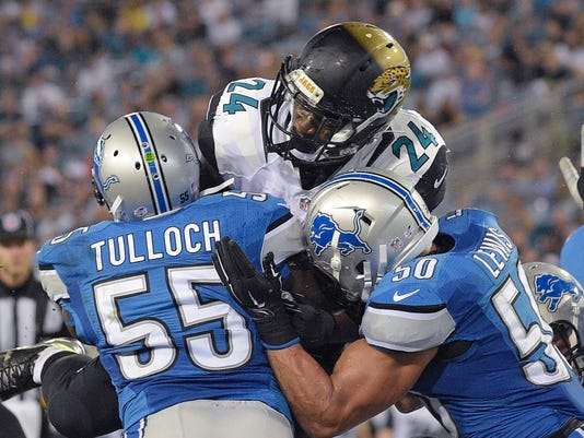 Jacksonville Jaguars running back T.J. Yeldon (24) dives for a 1-yard touchdown as Detroit Lions middle linebacker Stephen Tulloch (55) and linebacker Travis Lewis (50) try to stop him during the first half of an NFL preseason football game in Jacksonville, Fla., Friday, Aug. 28, 2015.( AP Photo/Phelan M. Ebenhack)