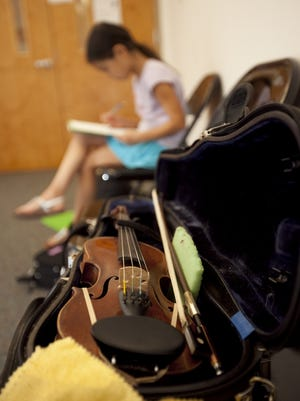 Violin student Katya Liton writes down notes of music with violin nearby during a lesson at the Music School of Delaware in this file picture. The school's Milford branch is moving to a bigger location.