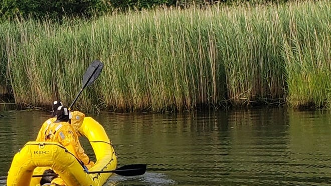 """Firefighters with the Centerville-Osterville-Marstons Mills Fire Department paddle an inflatable """"banana boat"""" over to reeds along the Herring River to rescue a woman stuck in the mud. She was taken to Cape Cod Hospital with minor injuries."""