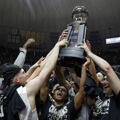 Members of the Purdue basketball team hold up the championship