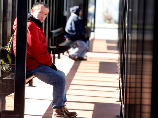 Richard Bradley stays warm in the covered and heated bus stop while waiting for the Rover bus in downtown Murfreesboro, on Thursday, Jan. 2, 2018.