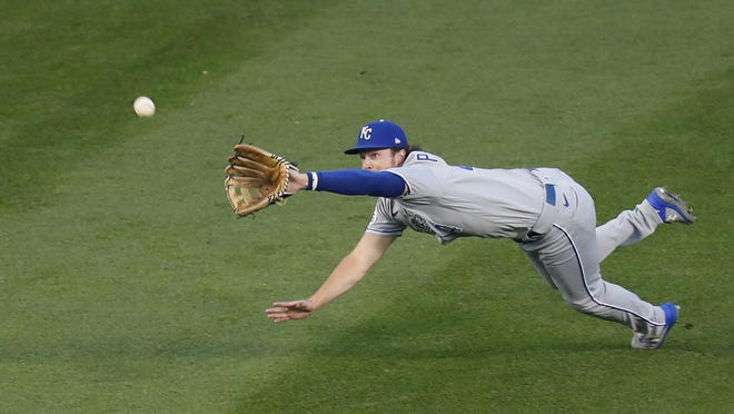 Kansas City Royals' Brett Phillips dives for, but is unable to catch a fly ball from Chicago Cubs' Kris Bryant during the first inning of a baseball game Monday, Aug. 3, 2020, in Chicago.