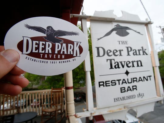 The Deer Park Tavern's old (right) logo on its Main Street sign and new logo at the Newark restaurant.