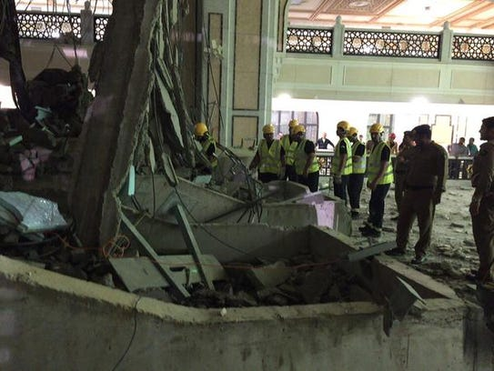 Civil defense workers examine the remains of a crane
