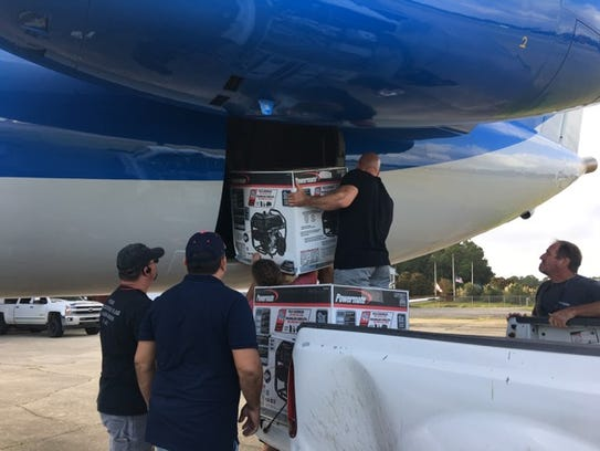 Generators are loaded onto a relief plane in Gulf Shores,