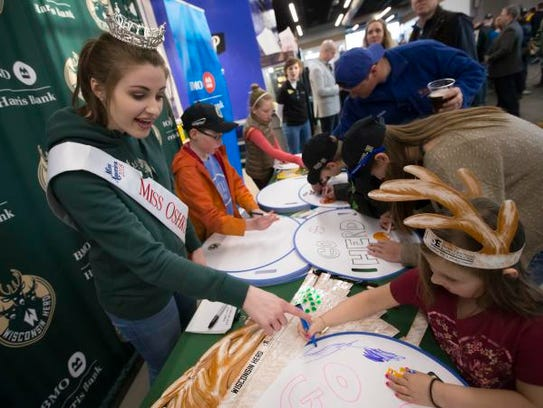 Miss Oshkosh Kate Lidtke assists Alaina Bradley with making a sign before a March 23 Wisconsin Herd game at Menominee Nation Arena in Oshkosh.
