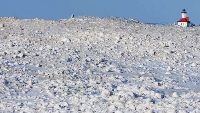 St. Joseph Lighthouse rises behind mounds of ice formed along the shores of Lake Michigan on Jan. 21, 2014, in St. Joseph, Mich.