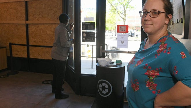 Store manager Emily Gandioso, 37, shows offof the two boarded-up windows at Starbucks, 502 State St., in Erie, on June 1, 2020. Two 10-foot-by-12-foot glass windows were shattered after a George Floyd killing peaceful protest in downtown Erie turned into a riot on May 30, 2020.
