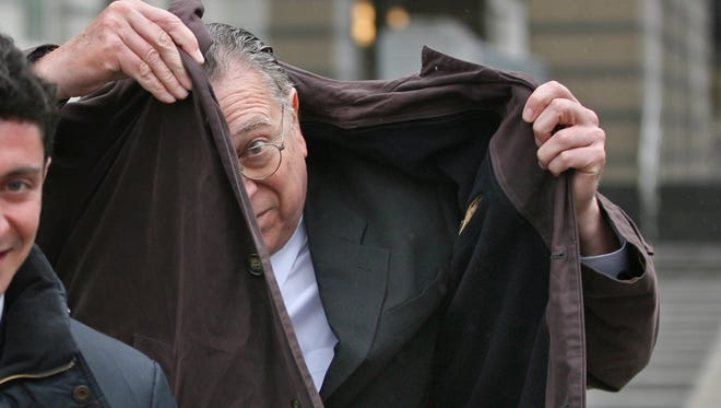 Albert Ades, 60, of Englewood, hides his face with his coat as he leaves federal court in Newark, Monday , March 14, 2016. Ades, a family medicine physician with offices in Cresskill and Little Falls, faced sentencing for defrauding Medicare, Medicaid and private insurance companies out of hundreds of thousands of dollars by billing them for non-existent office visits.