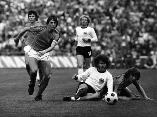 """Dutch forward Hendrik Johannes Cruijff """"Johan Cruyff"""", left, runs past German defender Paul Breitner, sitting on the pitch on July 7, 1974 during the finals of the Soccer World Cup at the Olympic Stadium in Munich, Germany."""