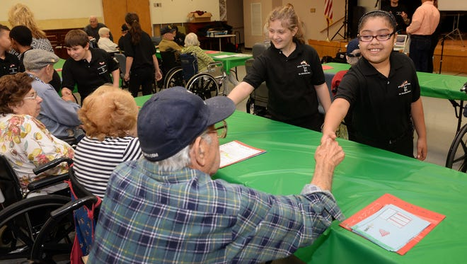 Mennies School Fine Arts Club members Jenny Espana and Melanie Spendiff (from right) introduce themselves to Veterans Memorial Home residents.