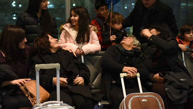 Sisters Sahira Jazrawi, 74, and Suad Jazrawi, 77, look up at their grand nieces and nephews after landing at Detroit Metropolitan Airport Tuesday night. The Chaldean sisters were supposed to arrive last week but were delayed due to the executive order that stopped refugees from seven countries, including Iraq where they are originally from. A stay on the order was issued by a federal judge allowing the sisters, who have spent 5 years in Jordan waiting for asylum, to join their family in the U.S. (Tanya Moutzalias/The Ann Arbor News via AP)