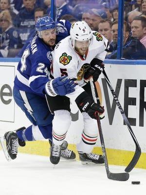 Chicago Blackhawks defenseman David Rundblad, right, knocks the puck away from Tampa Bay Lightning right wing Ryan Callahan.