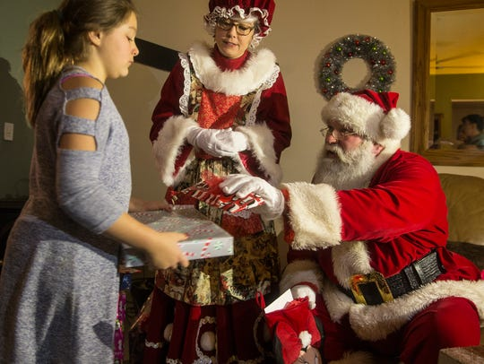 Santa's helper Jim Mitchell of Jackson delivers gifts