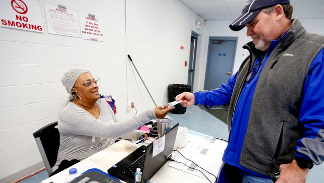 Yolanda Sharp, signs in Phillip Callahan, as he Calahan votes during early voting at SportsCom in Murfreesboro on Wednesday, Jan. 17, 2018.
