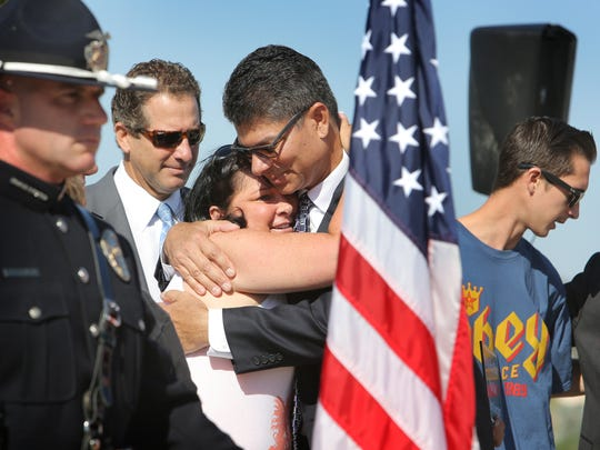 Jenifer Clark, widow of fallen police officer Michael Clark, receives a hug from Simi Valley City Council member Glen Becerra during a ceremony to honor the late officer.