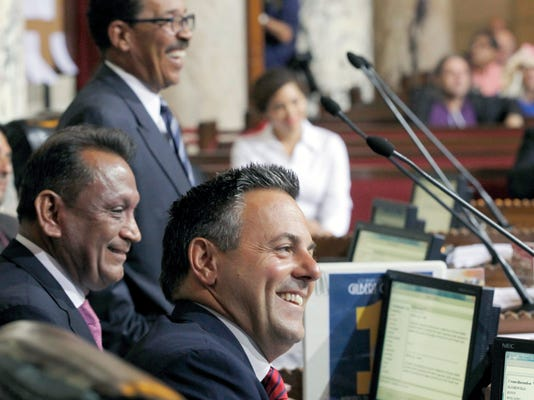 Los Angeles City Council President Herb Wesson, top left,  Councilman Gilbert Cedillo, left, and Councilman Joe Buscaino smile after a city council vote in Los Angeles, Tuesday, Sept. 1, 2015. Los Angeles City Council cleared the way for the city mayor to strike agreements for a 2024 Olympics bid, putting the city on the verge of becoming the U.S. contender after Boston's awkward collapse. (AP Photo/Nick Ut)