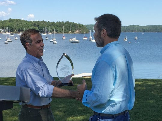 Steve Costello, left, of Green Mountain Power presents the 2016 Zetterstrom Environmental Award to James Ehlers of Lake Champlain International on Thursday, June 30, 2016, at Bayside Park in Colchester. The award, named for Milton resident and osprey advocate Meeri Zetterstrom, recognizes Ehlers' work on behalf the lake and water quality.