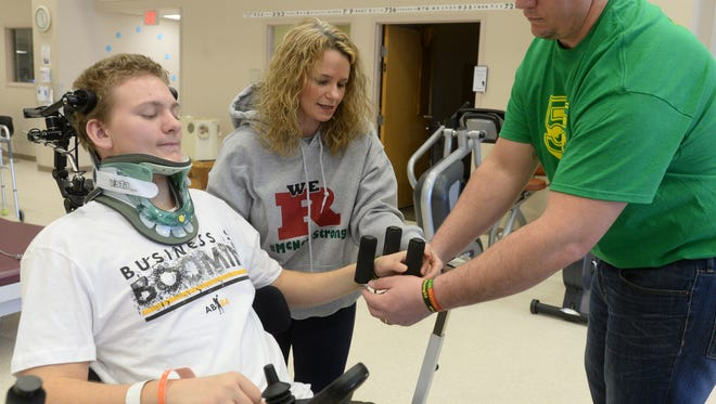 Teresa McNew and Michael McNew demonstrate one of the exercises Austin McNew works on as part of his rehabilitation Saturday, Feb. 13, 2016 at the Rehabilitation Hospital of Indiana in Indianapolis.