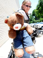 """Christina """"Squirrel"""" Verner rides with a teddy bear given to her by one of the children she's helped empower."""