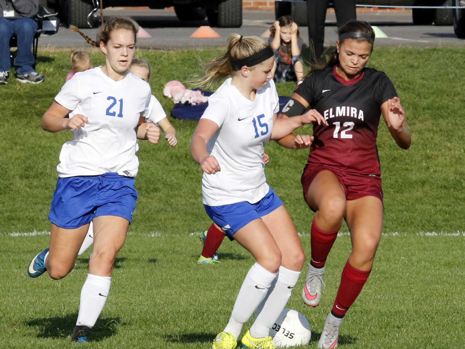 Elmira's Meredith Fennell and Horseheads' Abby Clark battle for possession as the Blue Raiders' Chelsey Seeley closes in during the teams' 1-1 girls soccer tie Thursday at Horseheads.